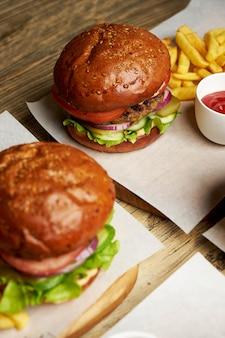 Set burger mit pommes frites und ketchup-sauce. große hamburger und pommes frites auf hölzernem tischhintergrund. fast-food-set hintergrund. restaurant burger menü