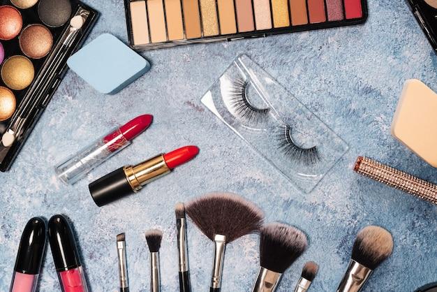 Set dekorativer kosmetik, make-up bürstet falsche wimpern auf blau