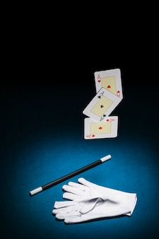 Set der spielkarte der asse; zauberstab und paar handschuhe auf blauem hintergrund