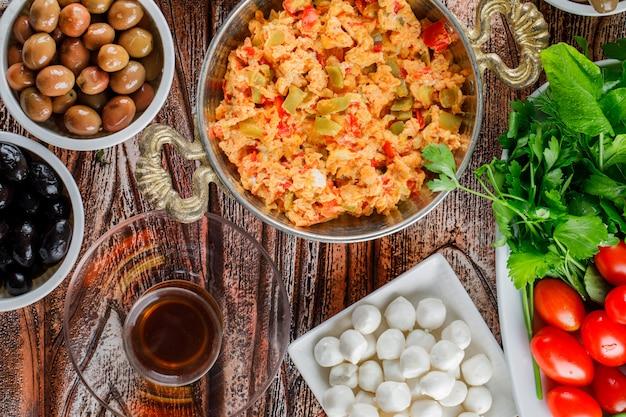 Set einer tasse tee, salat, gurken und köstliche mahlzeit in einem teller auf einer holzoberfläche