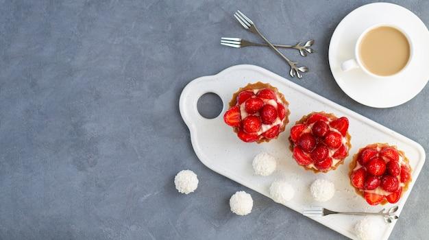 Set erdbeertörtchen oder beeren-minikuchen mit tasse kaffee und süßigkeiten. sommer dessert tisch draufsicht
