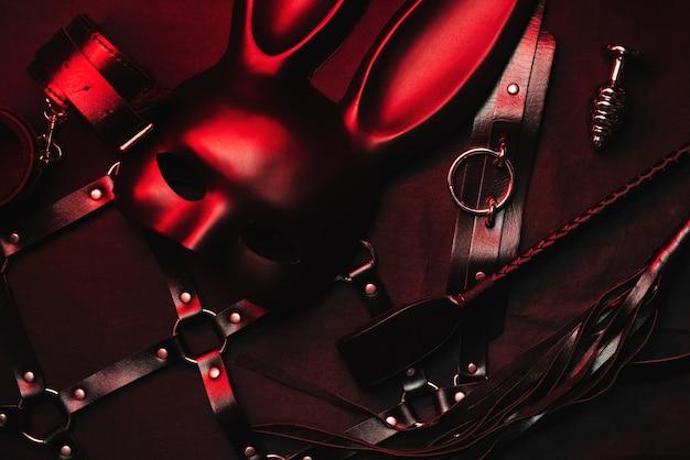 Set erotisches spielzeug aus einem sexshop. maske, ledergürtel, halsband, handschellen, peitsche und analplug