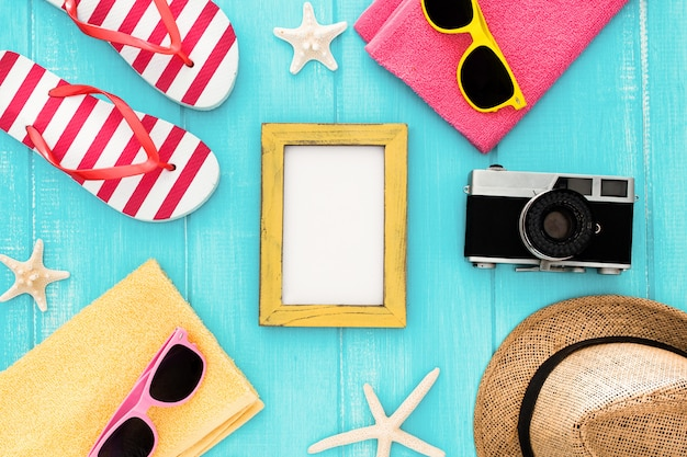 Set für einen strandurlaub am meer: handtuch, sonnenbrille, hart, kamera, rahmen und sonnencreme