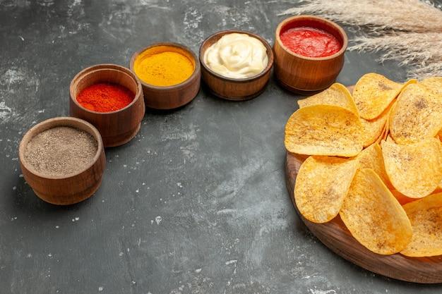 Set für kartoffelchips mit verschiedenen gewürzen mayonnaise und ketchup auf grauem tisch