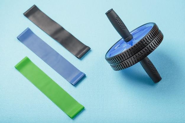 Set für sport, blaue rolle für bauchmuskeln, gummibänder für fitness auf einer blauen trainingsmatte.