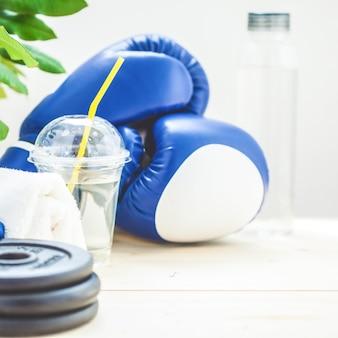 Set für sport, handtuch, boxhandschuhe, hantel und eine flasche wasser an einem licht
