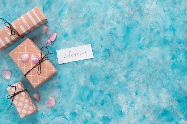 Set geschenkboxen in der nähe von tag mit titel und blütenblättern
