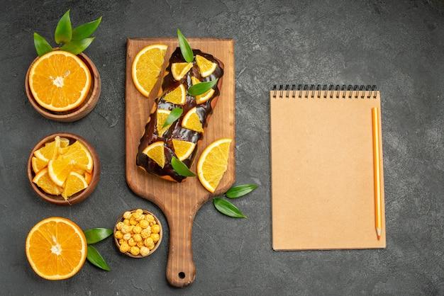 Set in zwei hälften geschnitten auf frische orangenstücke und weiche kuchen auf schwarzem tisch geschnitten