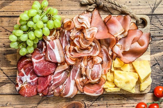 Set kaltgehärtetes italienisches fleisch schinken, schinken, pancetta, speck mit parmesan und traube.