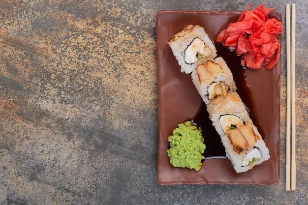 Set köstliches sushi mit stäbchen und ingwer auf marmoroberfläche