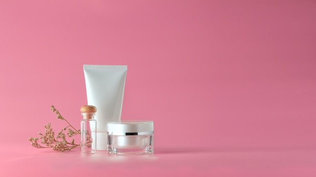 Set kosmetische produkte auf rosa hintergrund. kosmetisches leeres etikett für branding-modell.