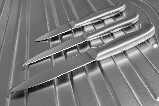 Set küchenmesser aus metall auf einer chromoberfläche