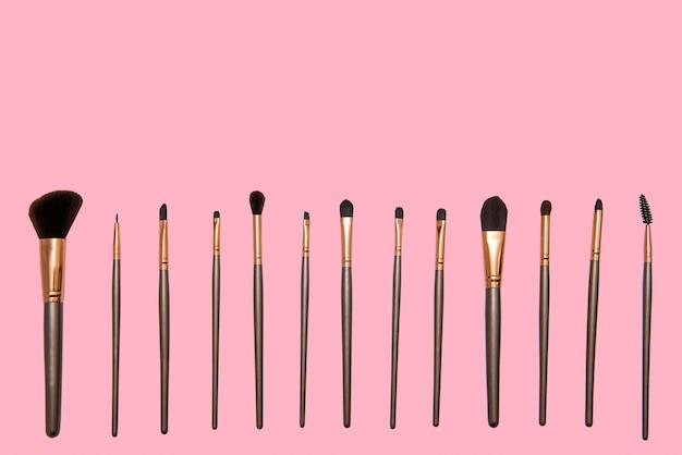 Set make-up-pinsel verschiedener typen und größen mit rosa hintergrund