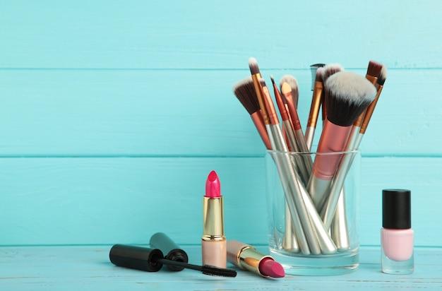 Set make-up-produkte auf blauem hintergrund. ansicht von oben