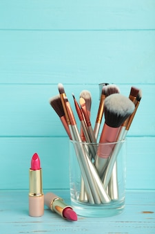 Set make-up-produkte auf blauem hintergrund. vertikales foto