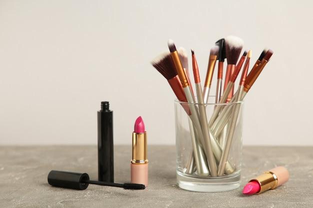 Set make-up-produkte auf grauem hintergrund. ansicht von oben