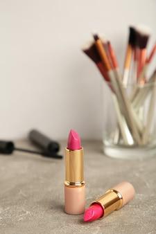 Set make-up-produkte auf grauem hintergrund. vertikales foto
