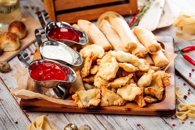 Set mini-chebureks und frühlingsrollen mit saucen