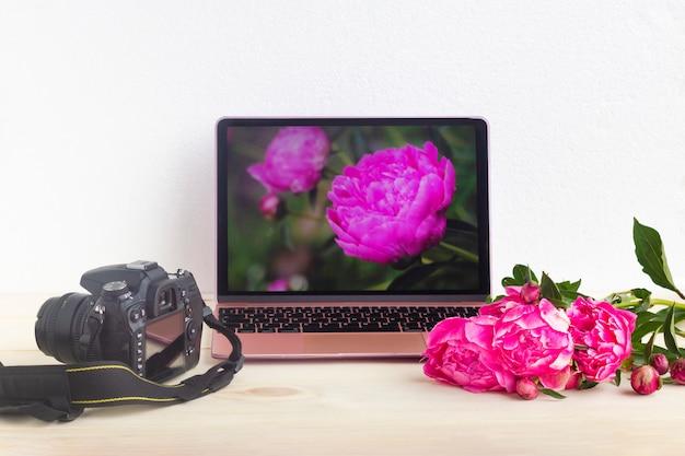 Set mit laptop, kamera und pfingstrosenblumen. blumen fotografieren. blumen auf dem computer.