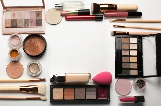 Set mit professionellen lidschatten-paletten, make-up-foundation und bronzer auf weißem hintergrund. freiraum