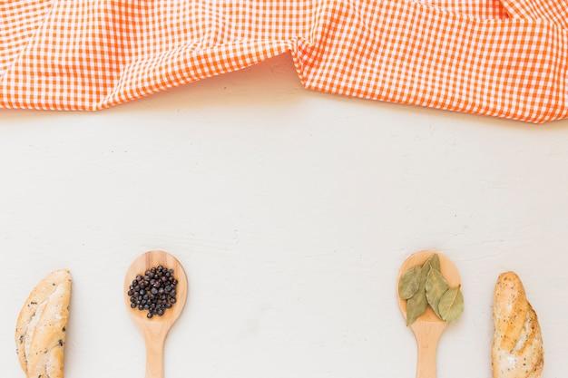 Set mit tischtuch löffel mit gewürzen und brot Kostenlose Fotos