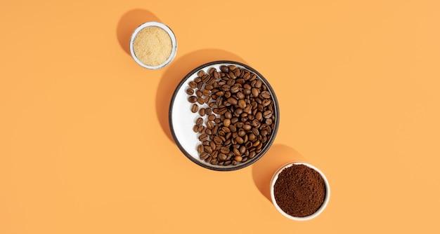 Set mit umweltfreundlichen kosmetikprodukten für zu hause spa zur selbstpflege. kaffeepeeling, brauner rohrzucker, kaffeebohnen auf einer keramikschale. hausgemachte anti-cellulite-kosmetik für peeling und spa-pflege. platz kopieren.