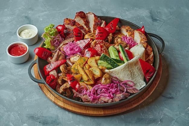 Set mit verschiedenen arten von gegrilltem fleisch. verschiedene gemüsesorten, würstchen, hühnchen, rindfleisch in einer pfanne auf grauer oberfläche