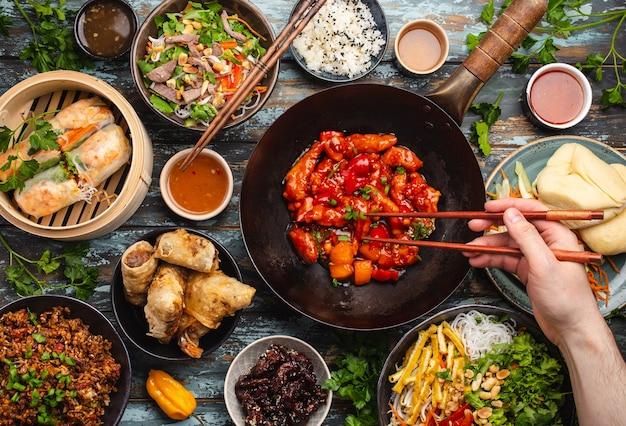 Set mit verschiedenen chinesischen speisen auf dem tisch mit männlicher hand, die essstäbchen von oben hält. voller und festlicher tisch mit allen traditionellen chinesischen gerichten, asiatisches abendessen oder buffet, draufsicht