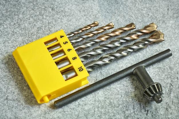 Set mit verschiedenen durchmessern von gewinnenden bohrern und einem bohrfutterschlüssel, nahaufnahme, geringe schärfentiefe