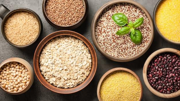 Set mit verschiedenen getreidekörnern und hülsenfrüchten auf steinhintergrund