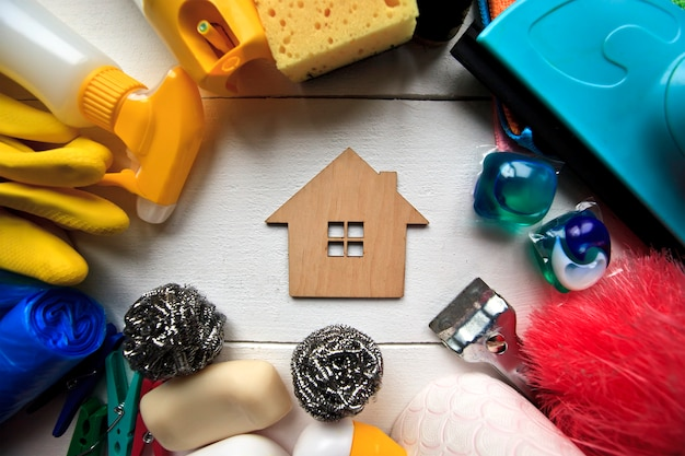 Set mit verschiedenen reinigungsgeräten auf holztisch und einem kleinen spielzeugschlauch in der mitte
