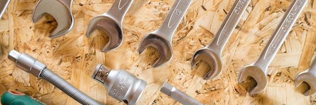Set mit verschiedenen reparaturhandwerkzeugen oder werkzeugen für automechaniker. reparatur-toolkit. ausrüstung für das bauen. hölzerner hintergrund, muster, draufsicht. banner