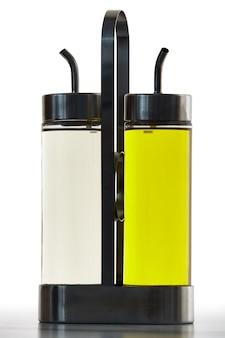 Set mit zwei flaschen für öl oder essig mit spenderauslauf in einem metallhalter.