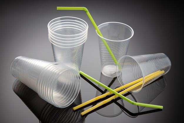Set neue leere plastikbecher und strohhalme. einweg-plastikmüll für getränke. nahansicht