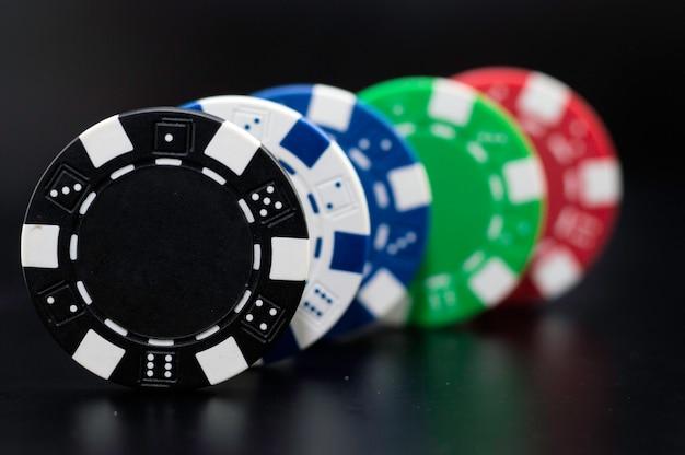 Set pokerchips von verschiedenen farben auf einem schwarzen hintergrund.