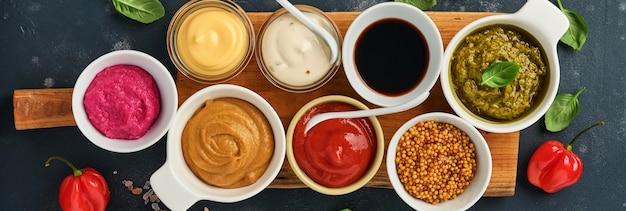 Set saucen in schalen - ketchup, mayonnaise, senf, sojasauce, bbq-sauce, pesto, chimichurri, senfkörner auf dunklem steinhintergrund. kopienraum der draufsicht.