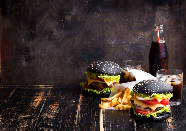 Set schwarze burger mit fleischpastetchen, käse, tomaten, mayonnaise, pommes frites und einem glas soda