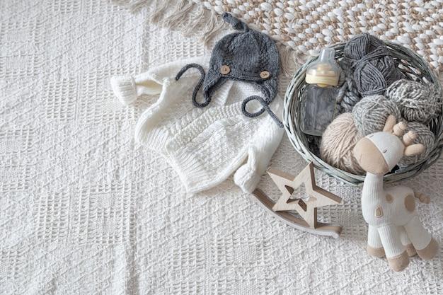 Set stilvolle handgefertigte strickkleidung für kinder mit verschiedenen accessoires im boho-stil, draufsicht.