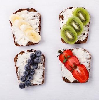 Set süße sandwiches mit frischkäse und frischen beeren und früchten