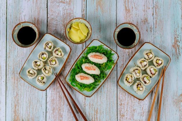 Set sushi-rolle mit sojasauce, ingwer und essstäbchen