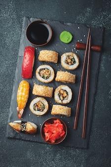 Set sushi und maki auf dunkler steintabelle.