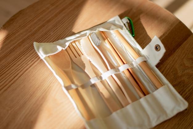 Set umweltfreundliches bambusbesteck auf holztisch. nachhaltiger lebensstil. plastikfreies konzept. nahaufnahme, draufsicht. schatten
