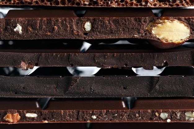Set verschiedene schokoladensorten mit nüssen, rosinen und früchten. vorbereitet für den weltschokoladentag