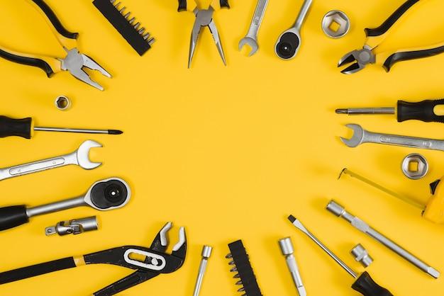 Set verschiedener bauwerkzeuge. werkzeuge für die reparatur zu hause. arbeiten sie auf einer baustelle. auf gelbem grund. rundweg. flatlay.