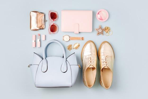Set von femininen accessoires mit handtasche, uhr, notiz, schönheitsprodukten und schuhen. flache lage, ansicht von oben. modekonzept in pastellfarben