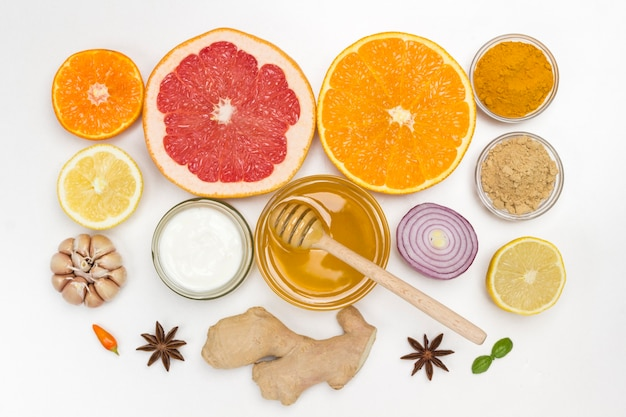 Set von gesunden lebensmitteln zur stärkung des immunsystems. zitrusfrüchte, ingwer, honig, knoblauch, zwiebeln. medizinische ernährung zu hause, grippeprävention. flach liegen