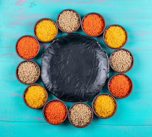 Set von großen schwarzen playe und verschiedenen linsen in einer braunen schale