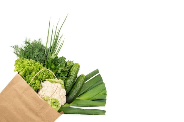 Set von grünen produkten in einer papiertüte auf weißem hintergrund