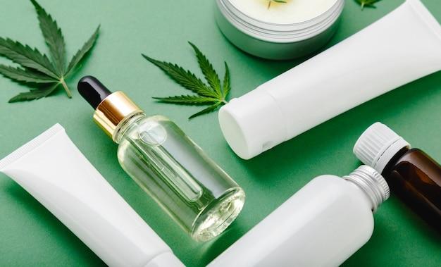 Set von hanf-hautpflegekosmetik in weißer mockup-verpackung. feuchtigkeitscreme, serum, lotion, cbd-öl, ätherisches öl aus cannabisblättern. flach auf grünem hintergrund legen.