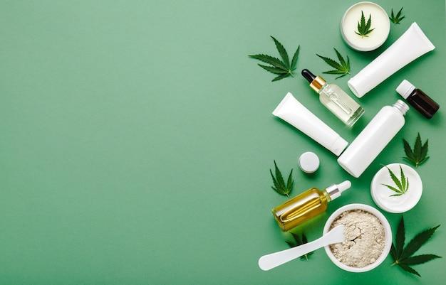 Set von hanf-hautpflegekosmetik in weißer mockup-verpackung. feuchtigkeitscreme, serum, lotion, cbd-öl, ätherisches öl aus cannabisblättern. flach auf grünem hintergrund mit kopienraum legen.